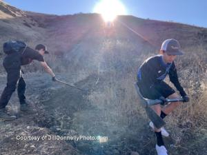 Volunteers (l to r) Brandon Altbush and Jack van der Brug of  the El Camino Real charter high school mountain bike team fill in a hole on the trail.Photo: Jill Connelly